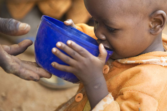 young boy drinking from cup