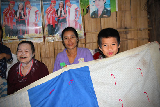 a young boy holds an LWR Quilt with two women behind him