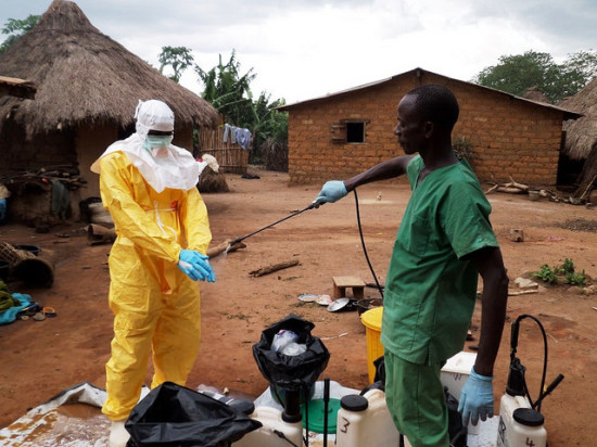 A healthworker helps clean off another worker in a hazardous materials suit in West Africa