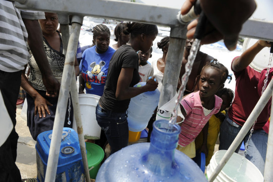People stand in line to fill containers with potable water at the Sainte Therese tent encampment in the Petionville section of Port-au-Prince