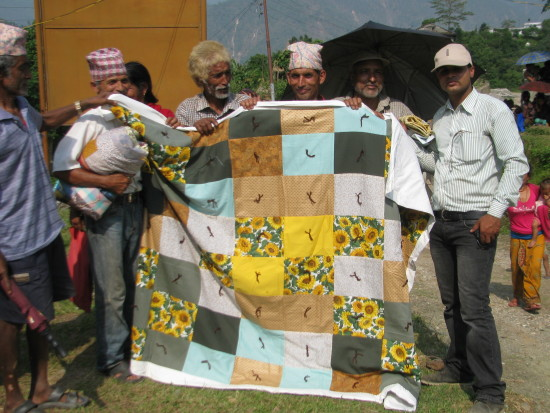 Men holding up quilt