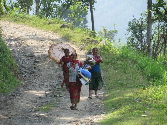 Women carrying quilts down hill