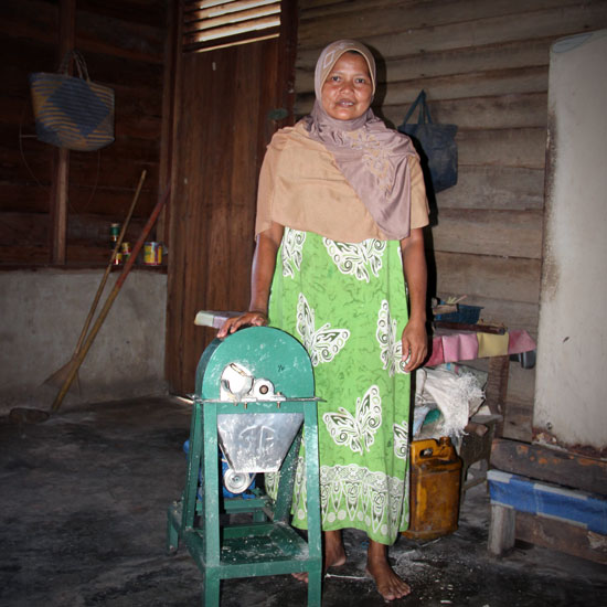 Hadi Raini stands alongside her cassava cutter