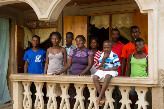 Lionel Philidor, center in purple, a member of the Sainte Helene coffee cooperative, poses for a photo with her extended family on the porch of her new home, which she was able to build with the proceeds from selling coffee seedlings, in Ouanaminthe, Haiti, June 17, 2015. She learned how to grow the seedlings and begin a plant nursery through her cooperative, in partnership with RECOCARNO, (Réseau des Coopératives Caféières de la Région Nord) the Network of Northern Coffee-Growing Cooperatives, and LWR. (photo by Allison Shelley for LWR)