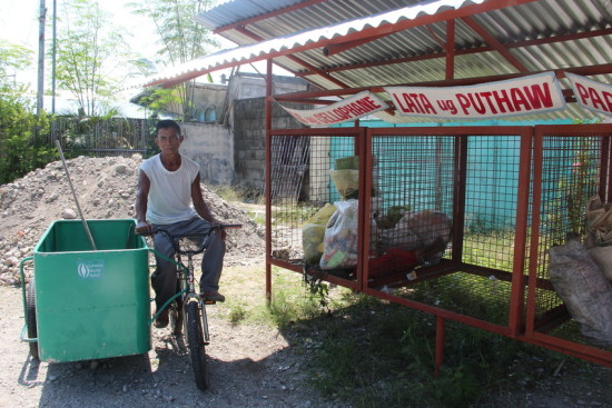 Antonio Rumando is paid to collect waste around Barangay Naungan and deposit it in MRFs. The collection bike, basket, and MRFs were provided through LWR's WASH program.