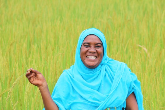 Rice farmer Mariam Abdallah stands in the midst of her thriving rice field near Dodoma, Tanzania. LWR works community groups in Tanzania to increase their knowledge, skills, and capacities to preserve and manage their natural resources in ways that improve their crop production - and as a result, their food security.