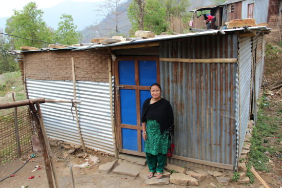 Picture from March-April 2016 site visits to Nepal Earthquake Response Program (NERP) in Lamjung and Gorkha Districts, Nepal. Picture of NERP beneficiaries from Kolki VDC in Lamjung. They received food packs, NFI/MR, shelter, and livelihood recovery support. Pictured: Jayanti Guru, Chairperson of one of the Ward's women's groups, standing beside her temporary shelter built in Kolki VDC, Lamjung with materials, like CGI sheets, provided by LWR. 10 family members live in this shelter with her.