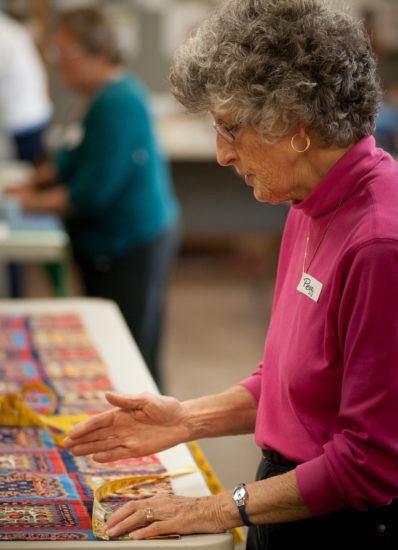 Peggy Sadler, a quilter from Our Savior Lutheran Church in Hanover, NH, lays out a quilt.