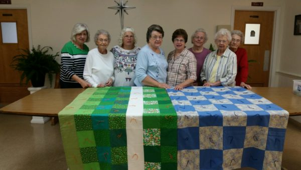 Group of quilters with two quilts