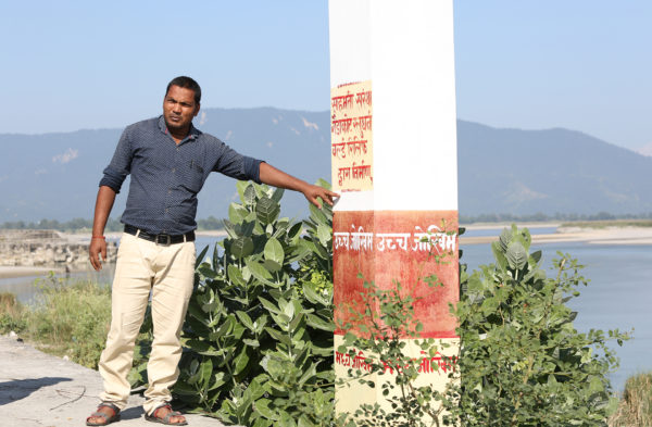 Ram Kisun Koiri stands next to his community's flood gauge and points to level where the Narayni River rose in 2017.