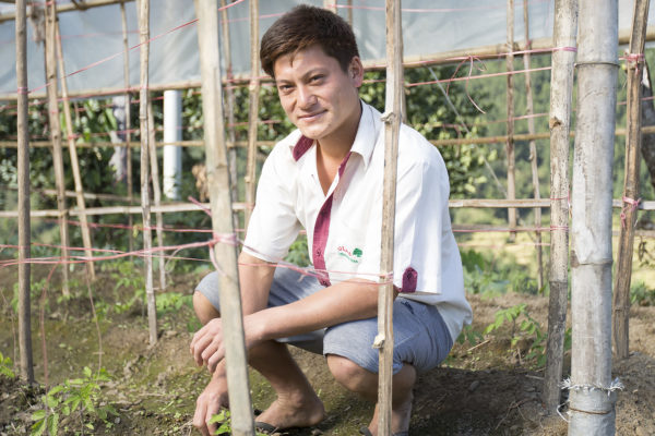 Santosh Gurung kneels in the nursery on his family's farm
