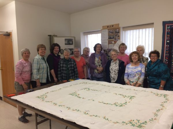 The quilters at Bristol Lutheran Church gather around a completed quilt. The group is known for using large sheets of fabric for their quilt tops.