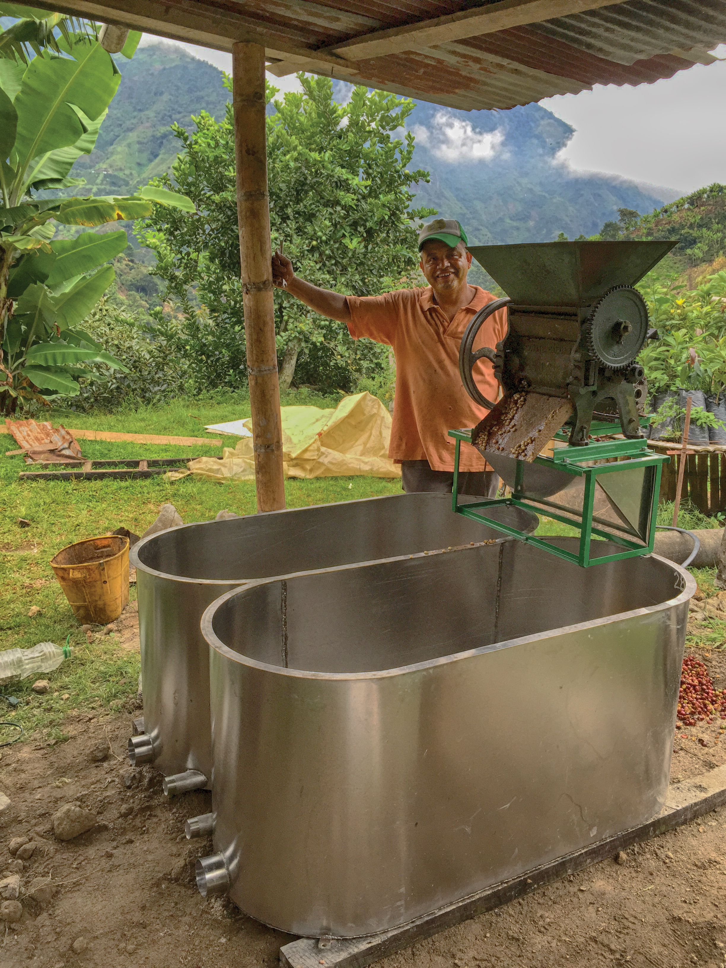 Don Oscar Ospina stands beside his new coffee washing tub.