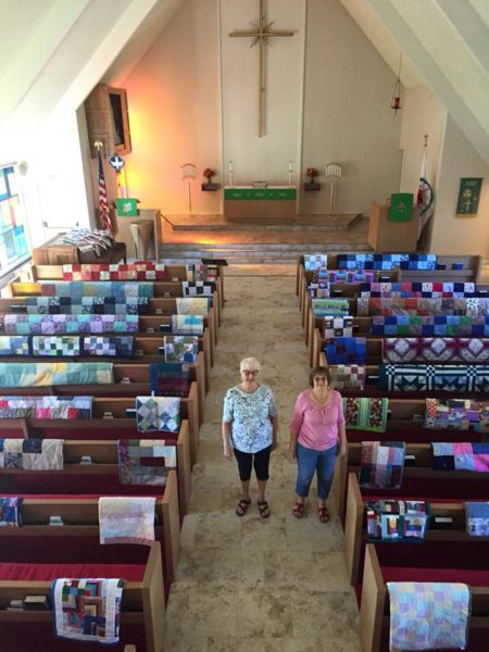 Overhead view of quilts in sanctuary with two quilters