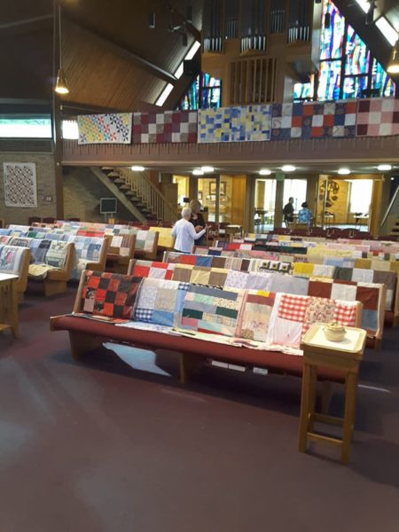 Multiple quilts on every pew, view from front of church