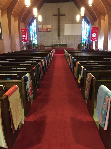 View down nave with quilts hung on side of pews