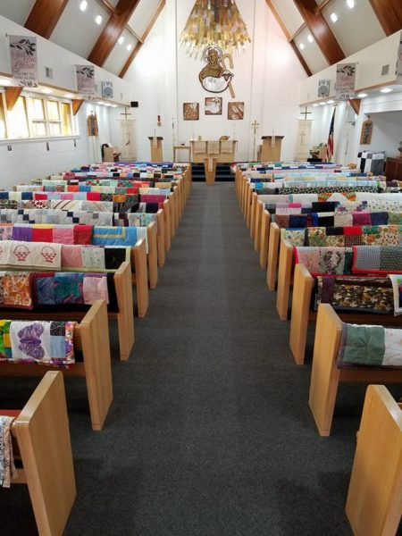 View down nave from back of sanctuary of quilts on pews