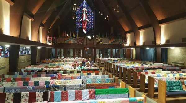 A view from the altar of the sanctuary covered in quilts, with the quilter posing in one of the pews