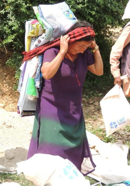 A woman leaves an LWR Mission Quilt distribution in Nepal's Lalitpur District after the April 2015 earthquakes [Photo: Carrie Taneyhill]