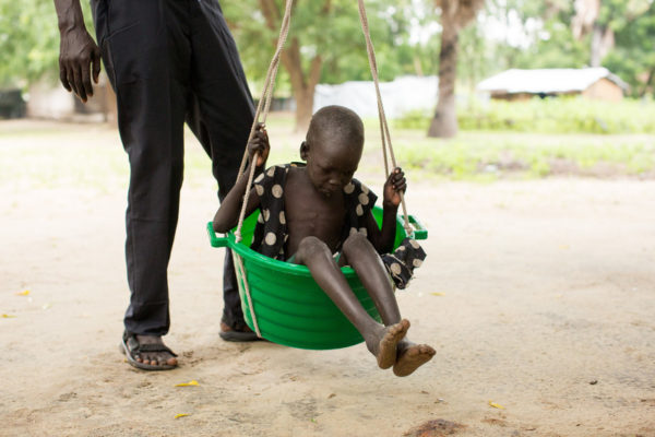 Sudanese child being weighed in a bucket-like container suspended from a rope.