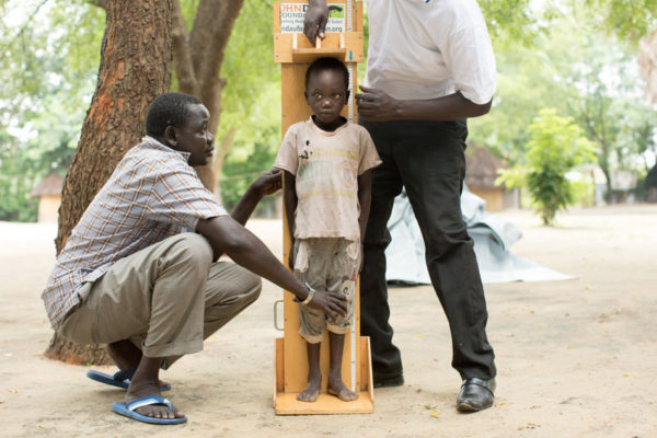 Adult man measures a child's height in South Sudan.