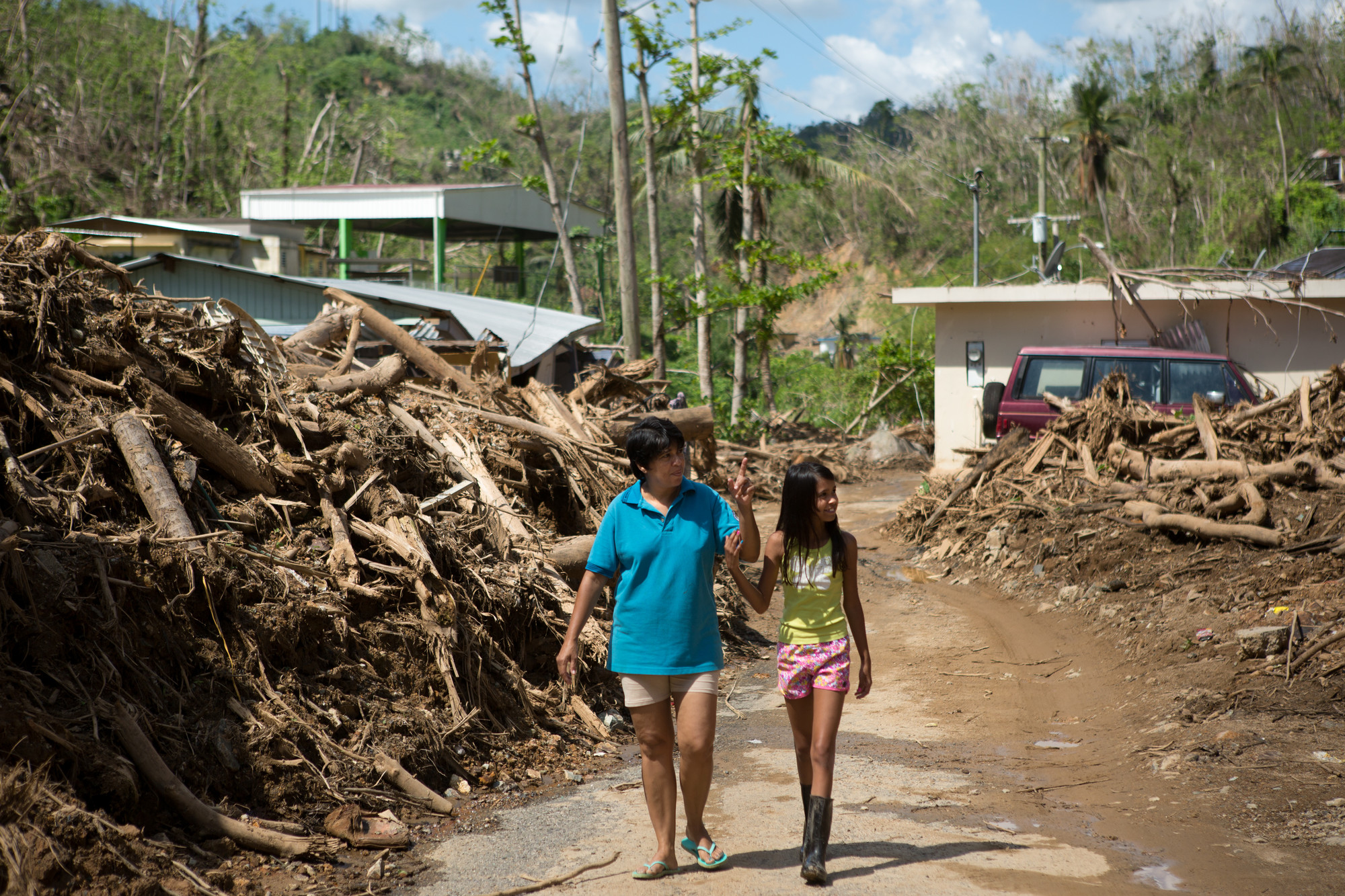 Igdalia Heredia Gonzalez, 49, and her daughter Valeria Gonzalez Jimenez, 11, walk through a cleared path in debris that all but buried their home during Hurricane Maria six weeks ago, in the town of Puente Blanco, in the municipality of Adjuntas, Puerto Rico, November 1, 2017.