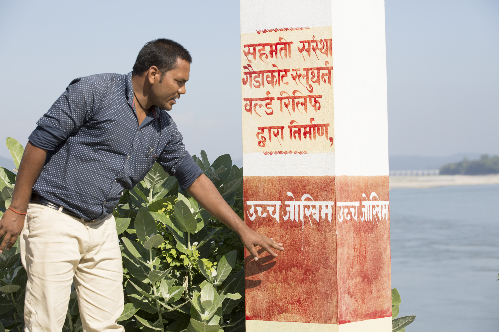 Ram Kisun Koiri, president of the local Community Disaster Management Committee (CDMC) in Narsahi, Nepal, shows visitors the flood gauge that measures water levels to indicate imminent flooding.