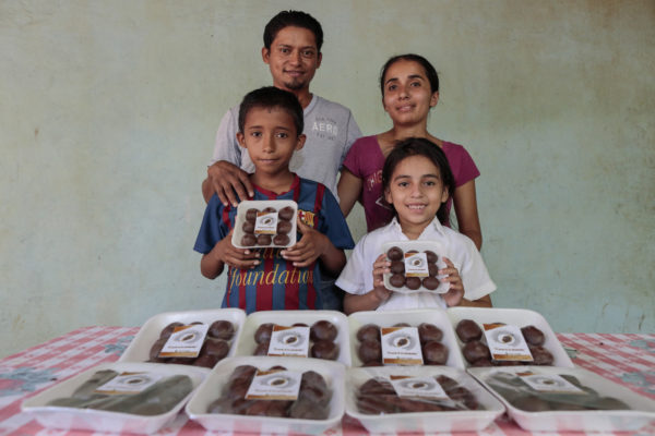 Willaims Savaria and his family pose with cocoa tablets he produces to sell.