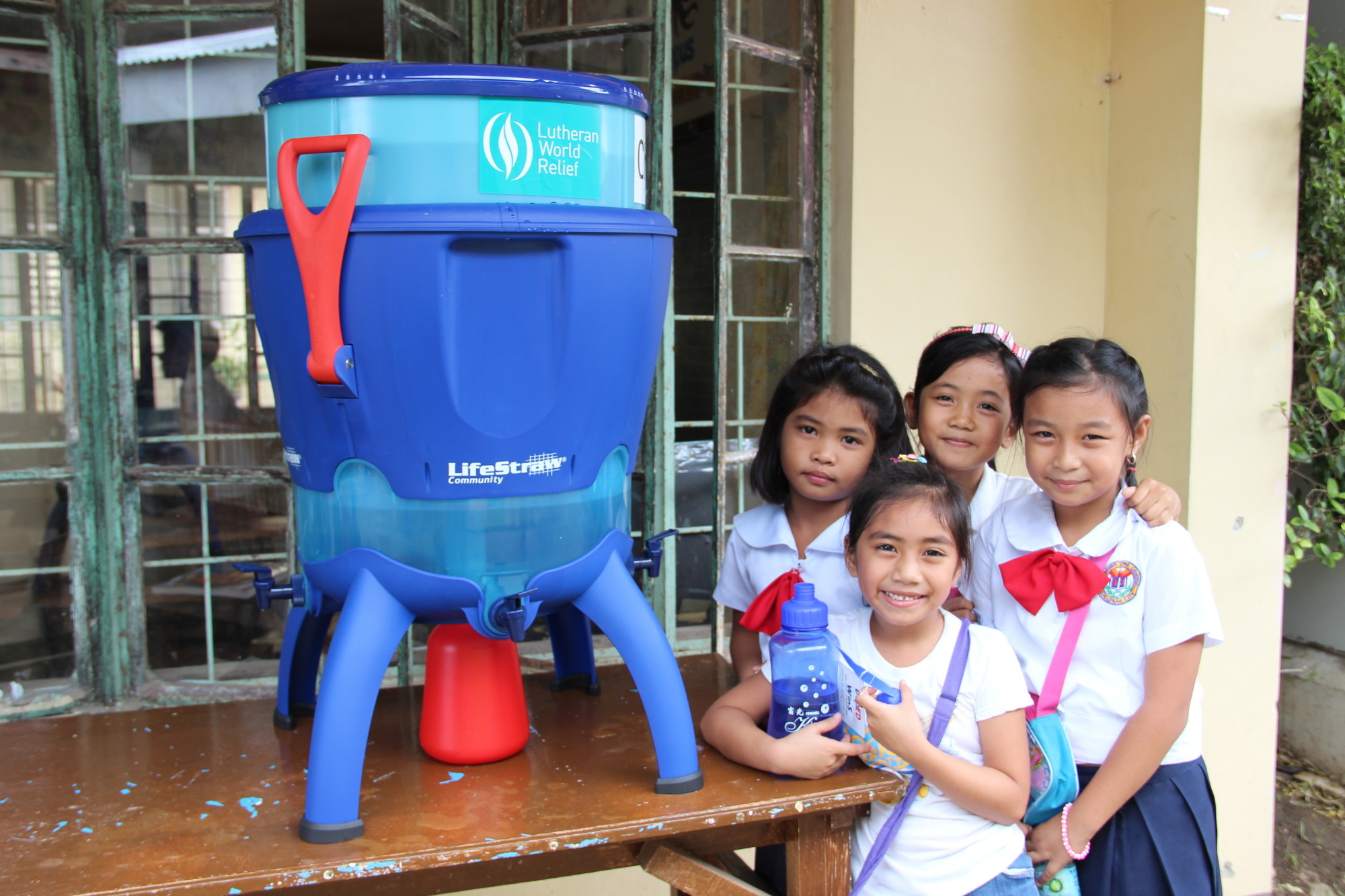 School children in the Philippines enjoy water from their Life Straw water filtration unit. These refillable water tanks hold 45 liters of water and can filter 12 liters per hour. These filters were distributed as a part of the response to Typhoon Haiyan, which struck the Philippines November 8, 2013.