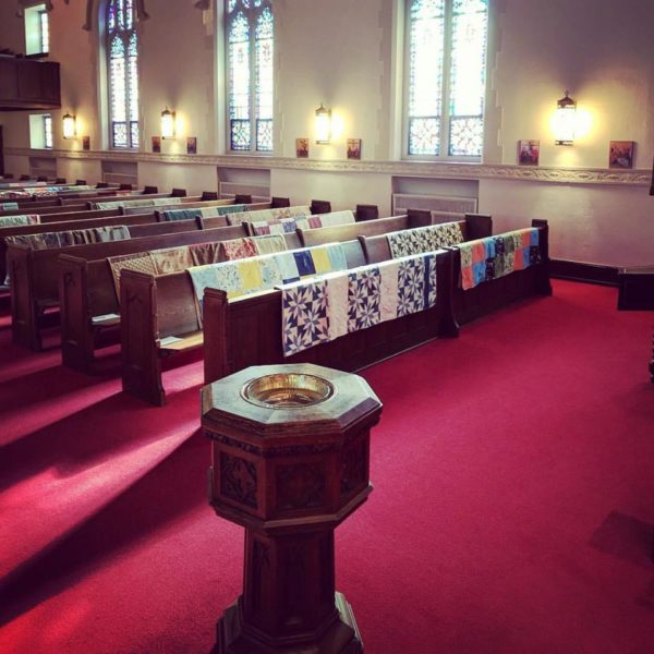 View from altar of quilts on pews on left side of sanctuary