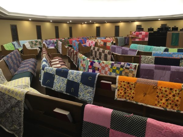 View from side of sanctuary of quilts on pews