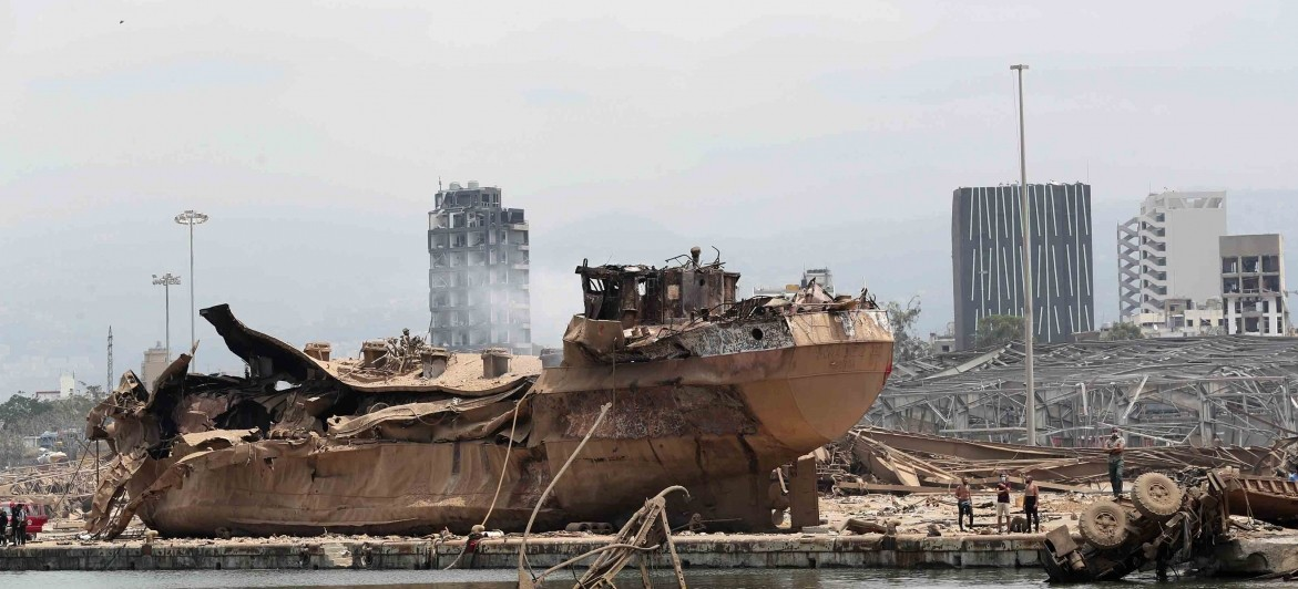 People stand by the wreckage of a ship at the devastated site of the explosion in the port of Beirut, Lebanon, Thursday Aug.6, 2020. (AP Photo/Thibault Camus, Pool)