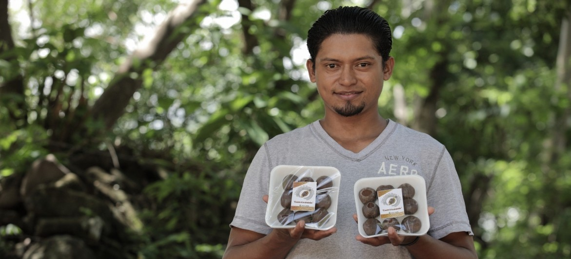 Williams Isidro Saravia, 30, shows the processed cocoa (in tablets used to make hot cocoa) he sells in his hometown Los Jicaros, just outside of San Miguel, El Salvador. (Photo by Oscar Leiva Marinero for Lutheran World Relief)