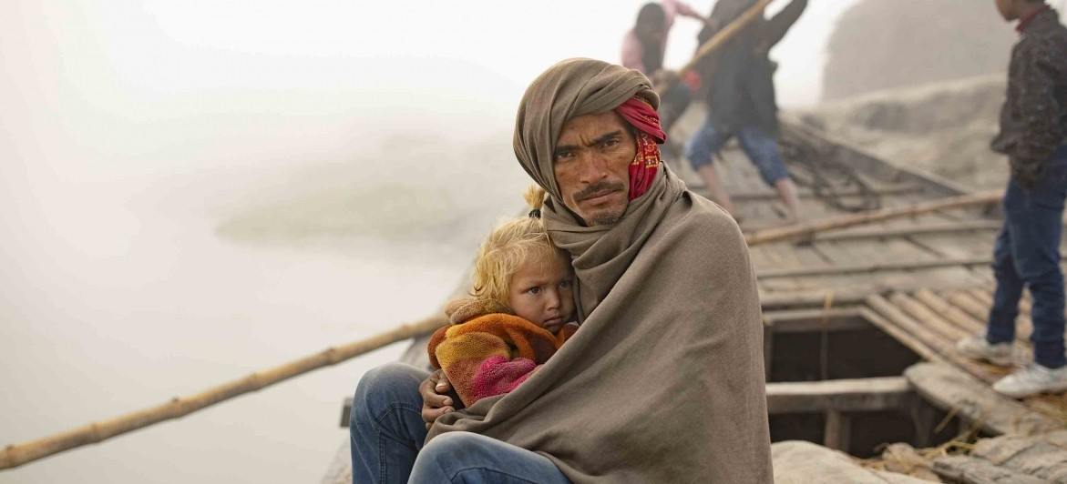 Rajendra Kushwaha, 36, seen here with his daughter Khushi Kumari, 4, boards a ferry boat each day to work in his fields across the Gandak River in Bihar, India. (Photo by Jake Lyell for Lutheran World Relief)
