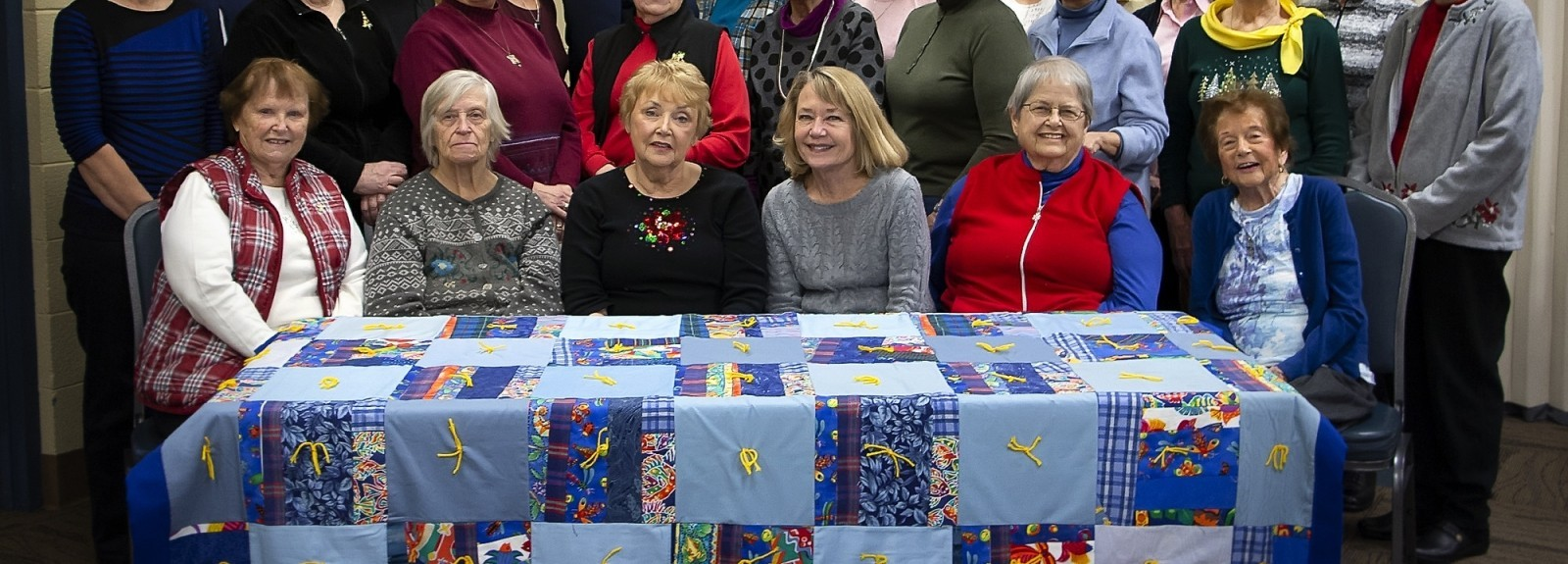 The quilting group at Gethsemane Lutheran Church in Hopkins, Minn. pose with a beautiful quilt they created.
