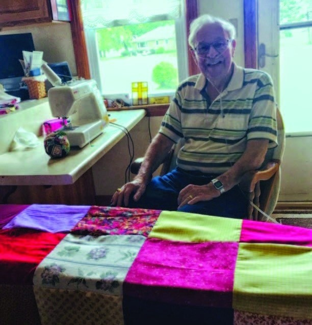 Bob Ashley sits at his sewing machine, where he made quilt tops as part of a 3-member quilting team at Immanuel Lutheran Church in LaSalle County, Ill.