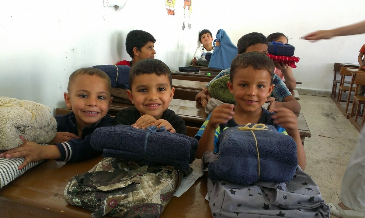 Syrian children enjoying their Personal Care Kits and School Kits they received at at the New Orthodox School in Jordan.