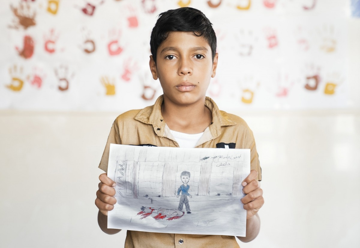 A young boy holds a graphic picture he drew of a man killed by Islamic State militants in Iraq