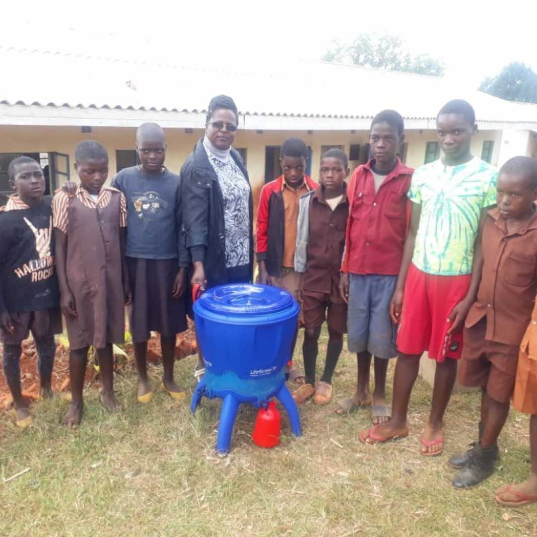 Students and a school staff member display their new water filter, provided to them by you after Cyclone Idai hit their community in March 2019. (Photo courtesy of Smile for Africa)