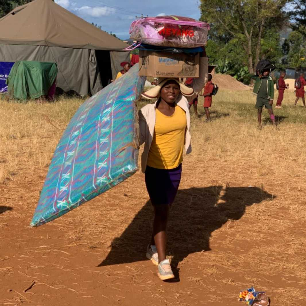 A woman carries a mattress and other items she received from a distribution carried out by our local partner, Smile for Africa, and made possible by you. (Photo courtesy of Smile for Africa)