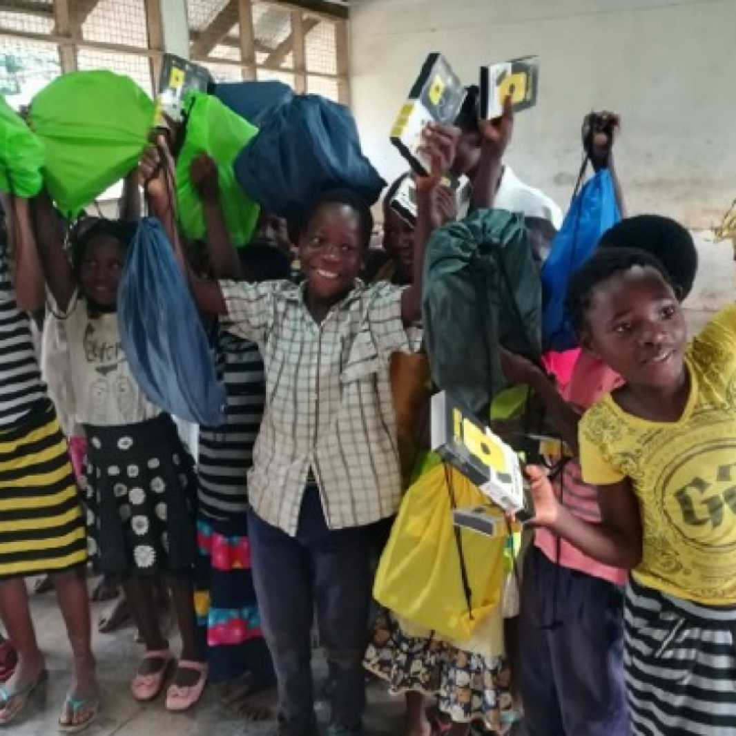 A class of students happily displays their new LWR School Kits in Mozambique. (Photo courtesy of Save the Children)