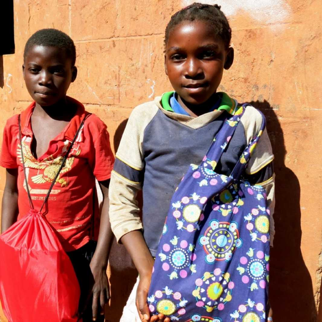 A boy and a girl happily display the LWR School Kits they received during a distribution in Mozambique. (Photo courtesy of Save the Children)